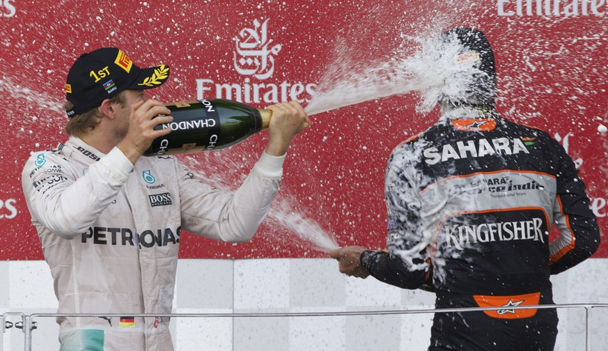 Mercedes driver Nico Rosberg of Germany, left, and Force India driver Sergio Perez of Mexico spray champagne after the Formula One Grand Prix of Europe at the Baku circuit in Baku, Azerbaijan, on Sunday, June 19, 2016. (AP Photo/Ivan Sekretarev)