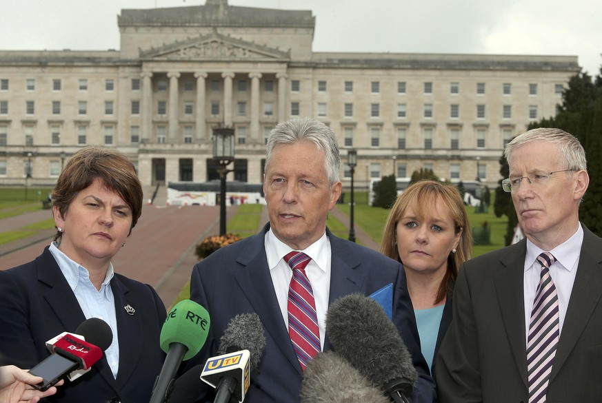 Democratic Unionist Party (DUP) leader Peter Robinson (C) speaks to the media in front of Parliament buildings in Belfast Northern Ireland September 9, 2015. - Northern Ireland's largest pro-British party threatened to bring down the province's power-sharing government after a senior member of the main Irish nationalist party Sinn Fein was arrested on Wednesday in relation to an IRA murder. Police suspect members of the IRA, a paramilitary group that is supposed to have disbanded under a 1998 peace deal, were part of the Aug. 12 shooting of Kevin McGuigan, destabilising the grand coalition and prompting crisis talks.REUTERS/Stringer