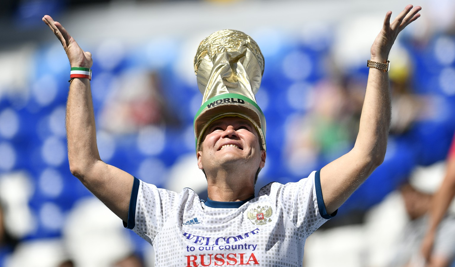 A fan with a hat depicting the World Cup trophy cheers prior to the group C match between Denmark and Australia at the 2018 soccer World Cup in the Samara Arena in Samara, Russia, Thursday, June 21, 2018. (AP Photo/Martin Meissner)