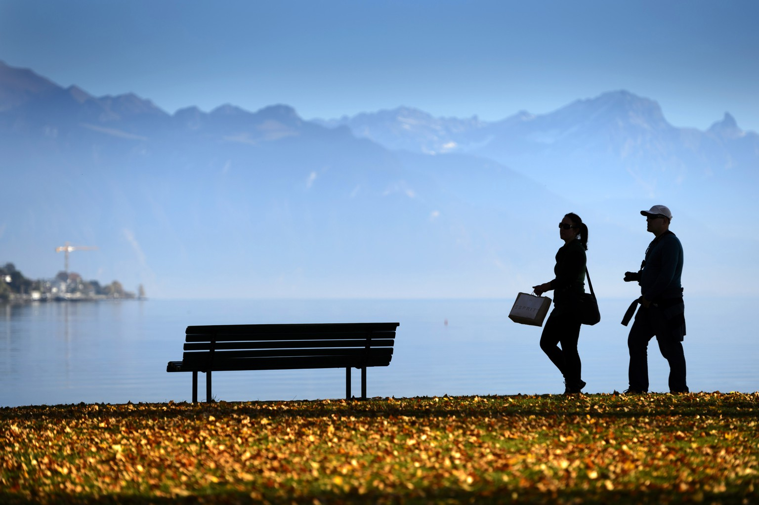 Two tourists walk and enjoy the sunshine on an unusually warm day on the shore of the Geneva Lake, in Lutry Beach near Lausanne, Southwestern Switzerland, Tuesday, November 10, 2015 as record-breaking temperatures for the month of November hit Switzerland. (KEYSTONE/Laurent Gillieron)