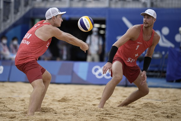Mirco Gerson, left, of Switzerland, takes a shot as teammate Adrian Heidrich watches during a men's beach volleyball match against Italy at the 2020 Summer Olympics, Friday, July 30, 2021, in Tokyo, Japan. (AP Photo/Felipe Dana) Adrian Heidrich,Mirco Gerson