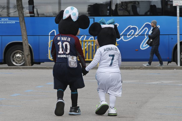 Two people dressed in Disney costumes, ply for tourist photos wearing shirts of Neymar and Ronaldo before a Round of 16, 1st leg Champions League soccer match between Real Madrid and Paris Saint Germain at the Santiago Bernambeu stadium in Madrid, Spain, Wednesday Feb. 14, 2018. (AP Photo/Paul White)