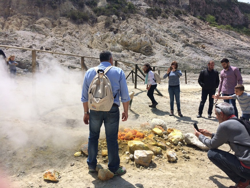 In this photo taken on Saturday, April 30, 2016, visitors look at steaming fumarolas at the Solfatara crater bed, in the Phlegraean Fields near Naples, Italy. Fields -- Campi Flegrei in Italian -- are a sprawling constellation of ancient volcanic centers. (AP Photo/Frances D'Emilio)
