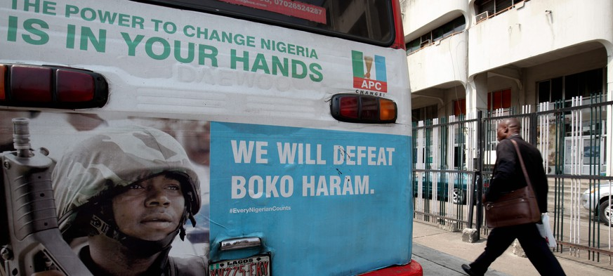 epa04617059 A man walks past an advertisement for the fight against Islamist militant group Boko Haram on the back of a public bus in Lagos, Nigeria, 12 February 2015. At least 15 people were killed on 12 February and several others were injured in an explosion at a crowded market in the north-eastern Nigerian town of Biu. No group has claimed responsibility for the attack, but the Islamists group Boko Haram has claimed responsibility for similar attacks in the past. Thousands of people have been killed in the last six years since Boko Haram embarked on a terror campaign to impose strict Islamic rule in Nigeria. Boko Haram has terrorized northern Nigeria, attacking police, schools and churches, as well as civilians and government buildings.  EPA/AHMED JALLANZO