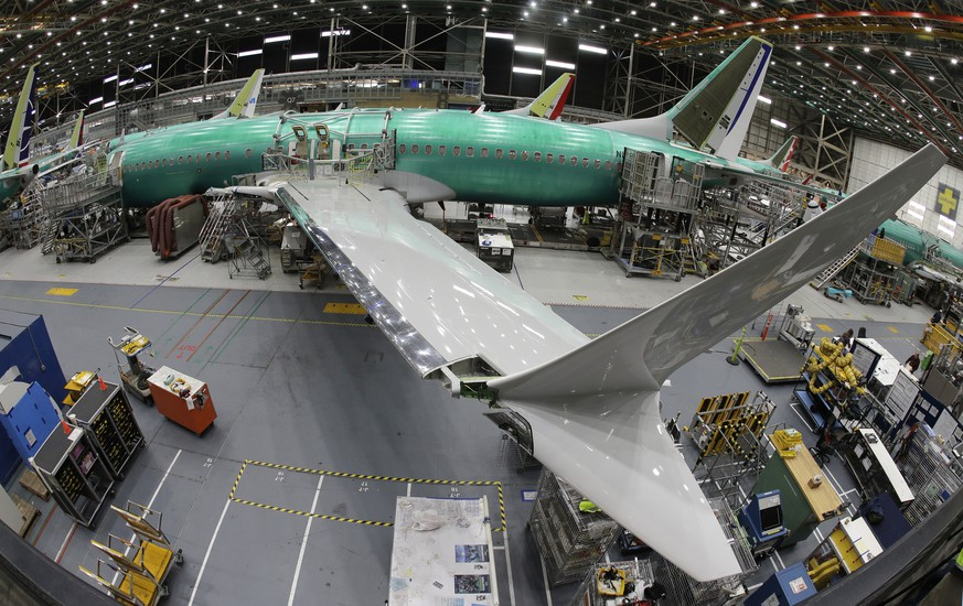 FILE- In this March 27, 2019, file photo taken with a fish-eye lens, a Boeing 737 MAX 8 airplane sits on the assembly line during a brief media tour in Boeing's 737 assembly facility in Renton, Wash. Boeing is cutting production of its grounded Max airliner this month to focus on fixing flight-control software and getting the planes back in the air. The company said Friday, April 5, that starting in mid-April it will cut production of the 737 Max from 52 to 42 planes per month. (AP Photo/Ted S. Warren, File)