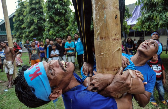 epa06703645 Indonesian laborers climb greased poles during a pole race to mark the May Day in Medan, North Sumatra, Indonesia, 01 May 2018. Labor Day, also known as International Workers' Day or May Day, is observed worldwide on 01 May.  EPA/DEDI SINUHAJI