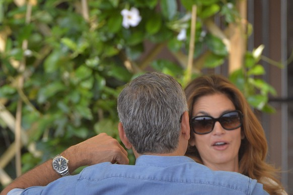 """US actor George Clooney chats with topmodel Cindy Crawford on September 27, 2014 at the Cipriani Hotel in Venice before his wedding with British Amal Alamuddin in Venice. George Clooney has said goodbye to bachelorhood in Venice with a stag party at his favourite restaurant with Hollywood chums, and was gearing up for a day of glamourous pre-wedding celebrations. The actor had swept into the floating city yesterday with his British fiancee Amal Alamuddin on a watertaxi dubbed """"Amore"""", zipping up the Grand Canal to cheers from fans at the start of nuptials set to draw out over the weekend.  AFP PHOTO / ANDREAS SOLARO"""