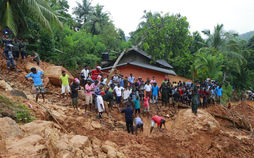 Sri Lankans watch military rescue efforts at the site of a landslide in Bellana village in Kalutara district, Sri Lanka, Friday, May 26, 2017. Mudslides and floods triggered by heavy rains in Sri Lanka killed more than a dozen people with four others missing, Home Affairs Minister Vajira Abeywardana said Friday. (AP Photo/Eranga Jayawardena)