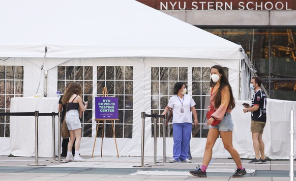 epa08617164 Medical personnel direct students arriving to a COVID-19 testing tent set up at New York University in New York, New York, USA, on 21 August 2020. All students returning to the school are being tested before the start of classes next month as schools around the country are trying to determine the safest way for classes to restart.  EPA/JUSTIN LANE