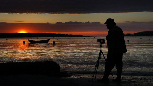 A brief appearance by the sun provides Chuck Johns with a dramatic backdrop as he photographs a dory moored off Willard Beach, Friday morning, May 17, 2019, in South Portland, Maine. The sun has been an infrequent visitor to the state in recent weeks. Another round of rain showers are expected to move in later in the day. (AP Photo/Robert F. Bukaty)