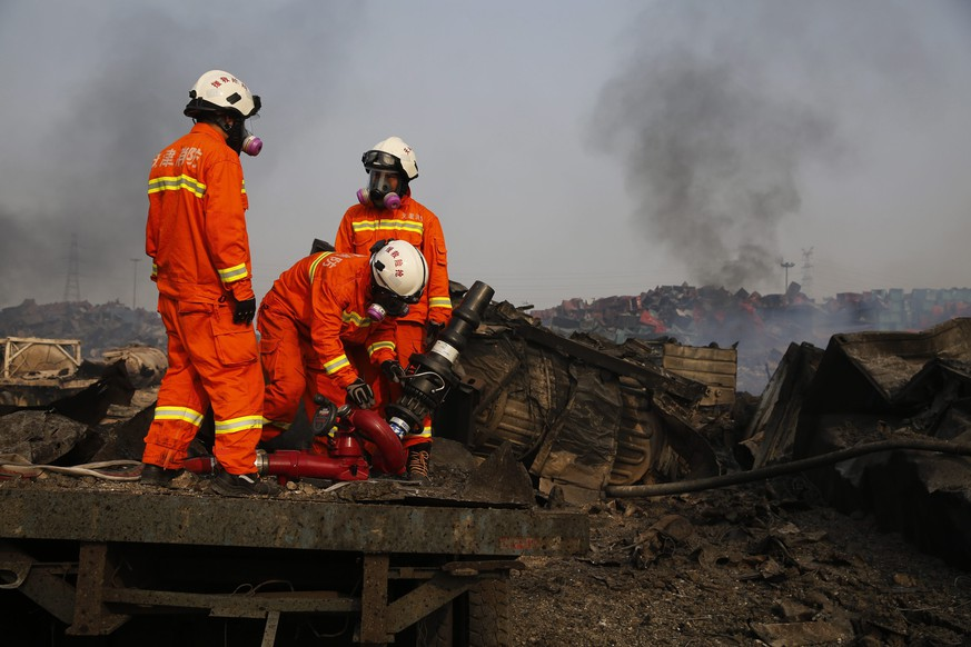 epa04884520 Firemen wearing gas masks prepare to combat fresh fires in the area of a huge explosion that rocked the port city of Tianjin, China, 15 August 2015. Explosions and a fireball at a chemical warehouse killed at least 85 people in the north-eastern Chinese port city of Tianjin late on 12 August. New explosions rocked a chemical warehouse in northern China as police ordered residents to evacuate buildings within a three-kilometre radius, state media said on 15 August.  EPA/WU HONG