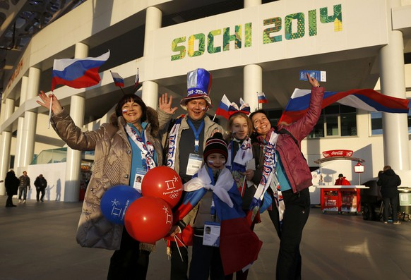People wave as they arrive for the opening ceremony of the 2014 Sochi Winter Olympics, February 7, 2014. REUTERS/Mark Blinch (RUSSIA  - Tags: OLYMPICS SPORT)