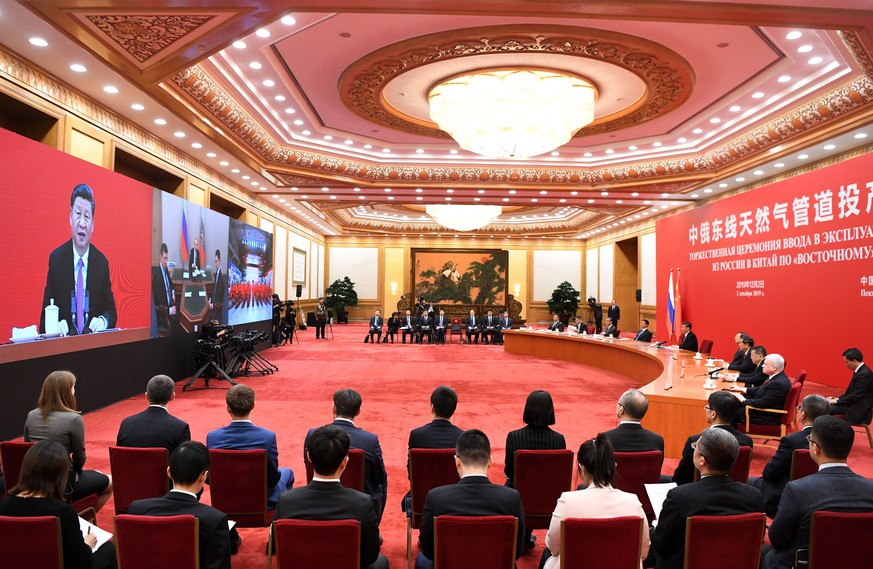 epa08039042 A general view shows China's President Xi Jinping speaking with Russian President Vladimir Putin via a video link, from the Great Hall of the People in Beijing, China, 02 December 2019.  EPA/NOEL CELIS / POOL