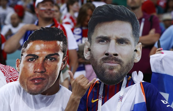 Fans wear masks with the face of the Portuguese national soccer star Cristiano Ronaldo and Argentina national soccer star Lionel Messi prior to the start of the quarterfinal match between Russia and Croatia at the 2018 soccer World Cup in the Fisht Stadium, in Sochi, Russia, Saturday, July 7, 2018. (AP Photo/Manu Fernandez)