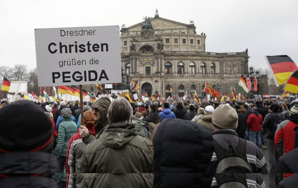 Protestors show a banner that reads: ' Dresden christians greet PEGIDA' during a rally of the group Patriotic Europeans against the Islamization of the West, or PEGIDA, in Dresden, Germany, Sunday, Jan. 25, 2015. (AP Photo/Michael Sohn)