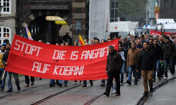 epa04435482 Kurds demonstrate against the violence of Islamic State (IS) militants holding a banner reading 'Stop the IS attacks on Kobani' in Bremen, Germany, 07 October 2014. Islamic State fighters advanced deep into the eastern districts of the beleaguered Kurdish holdout of Kobane amid fierce street fighting, a monitoring group said.  EPA/CARMEN JASPERSEN