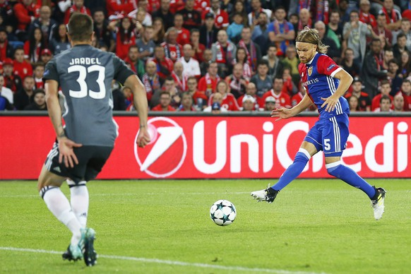 epa06230820 Basel's Michael Lang (R) score the 1-0 lead against Benfica's Jardel (L) during the UEFA Champions League group A soccer match between FC Basel 1893 and Benfica Lisbon in the St. Jakob-Park stadium in Basel, Switzerland, 27 September 2017.  EPA/PETER KLAUNZER