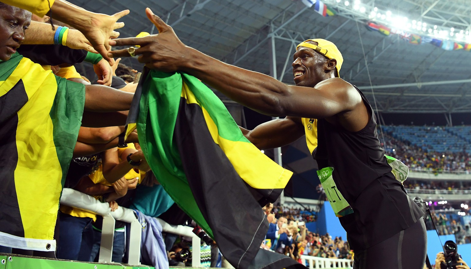epa05486043 Usain Bolt of Jamaica celebrates with fans after winning the men's 100m final of the Rio 2016 Olympic Games Athletics, Track and Field events at the Olympic Stadium in Rio de Janeiro, Brazil, 14 August 2016.  EPA/BERND THISSEN
