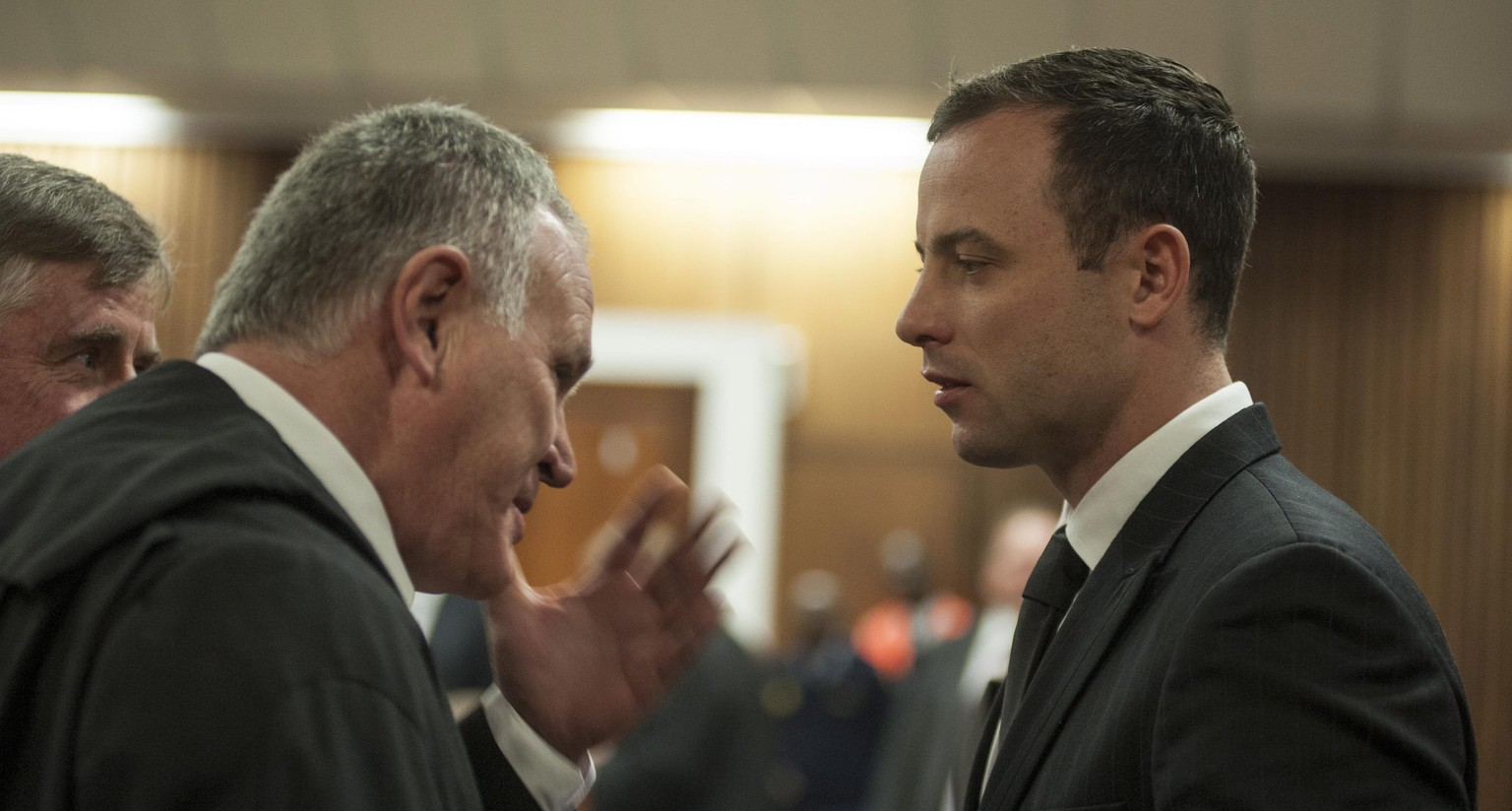 epa04291102 South African Paralympic athlete Oscar Pistorius (R) speaks with his defence lawyer Barry Roux (L) in the dock during his ongoing murder trial at a Court in Pretoria, South Africa, 30 June 2014. Pistorius stands trial for the premeditated murder of his model girlfriend Reeva Steenkamp in February 2013.  EPA/IHSAAN HAFFEJEE / POOL