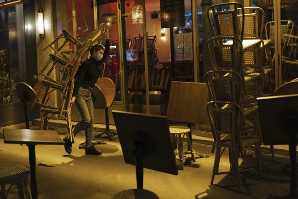 A woman carries chairs to close a bar terrace in Paris, Monday Sept. 28, 2020. French President Emmanuel Macron justified on Monday new restrictions in the country to limit the spread of the virus as restaurant and bar owners forced to shut down expressed anger at the measures. Milder restrictions have been ordered in ten other cities including Paris, with gyms shut down, public gatherings of more than 10 people banned and bars ordered to close at 10 p.m. (AP Photo/Francois Mori)