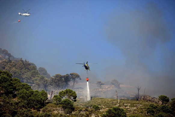 epa04290256 Two helicopters spread water over a the area during a forest fire next to the village of Competa, in Costa del Sol, southern Spain, 29 June 2014. The fire, which broke out in Sierra de Tejada hills, caused several residents to be evacuated.  EPA/CARLOS DIAZ