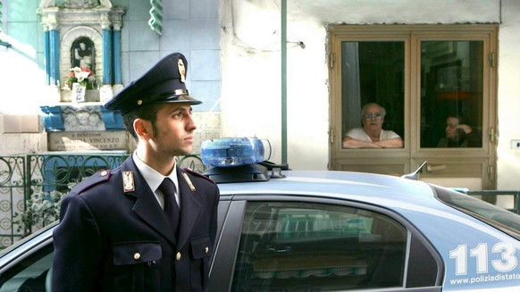 Two Neapolitian citizens on background observe an Italian policeman on guard during a large police operation against Camorra suspects in Naples'