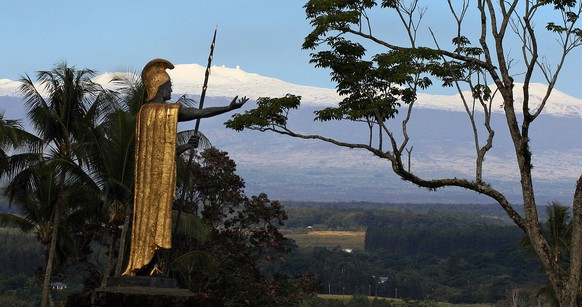 Snow on Mauna Kea is seen Friday Jan. 31, 2014, behind a statue of the Hawaiian King Kamehameha in Hilo, Hawaii. The dormant volcano and highest point in Hawaii got a fresh blanket of snow earlier in the week with 6 to 12 inches at the 10,000 foot level. (AP Photo/Tim Wright)