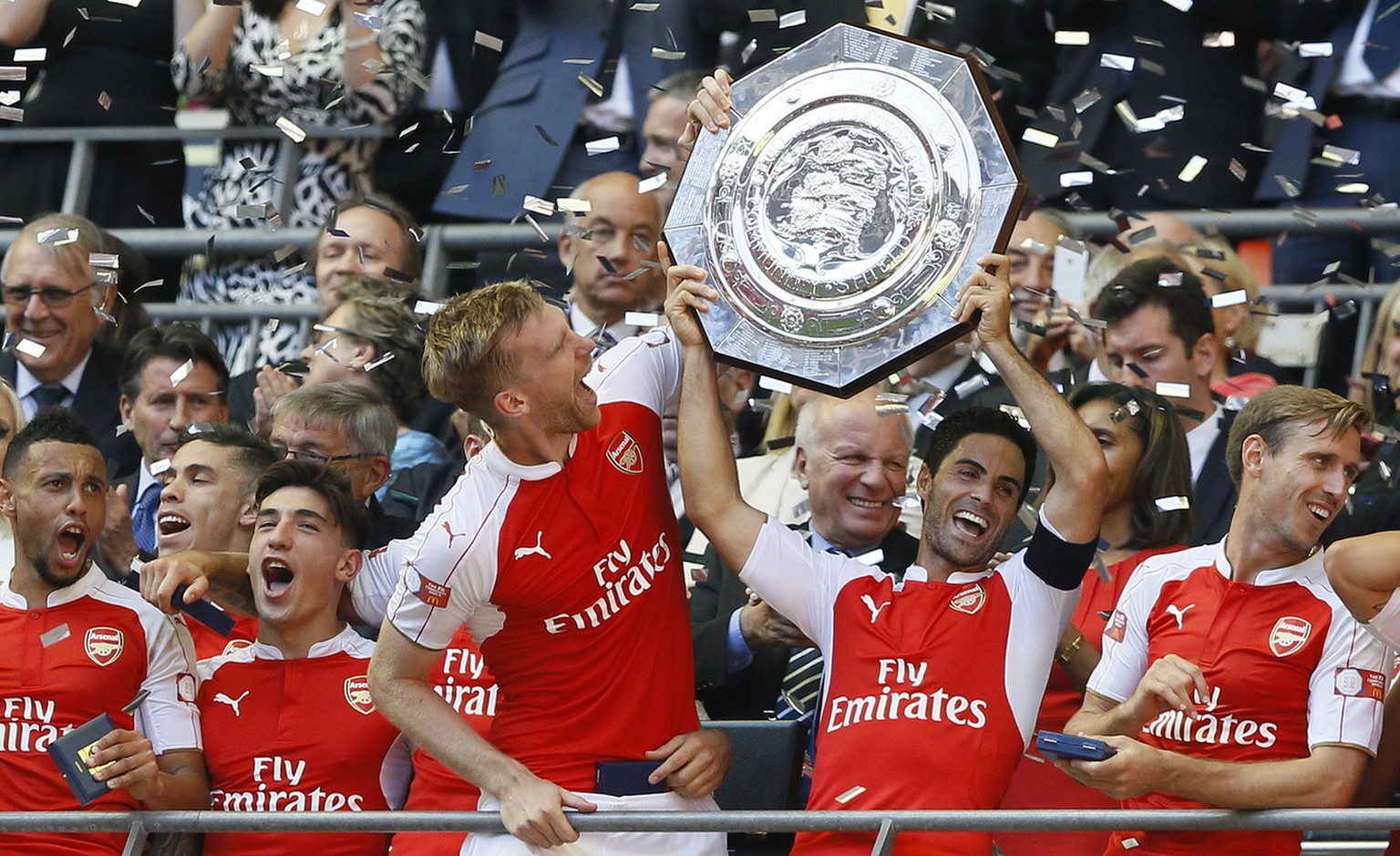 Arsenal's captain Per Mertesacker, centre, holds the trophy with Mikel Arteta, second right, after winning the English Community Shield soccer match between Arsenal and Chelsea at Wembley Stadium in London, Sunday, Aug. 2, 2015. Arsenal won the match 1-0. (AP Photo/Kirsty Wigglesworth)