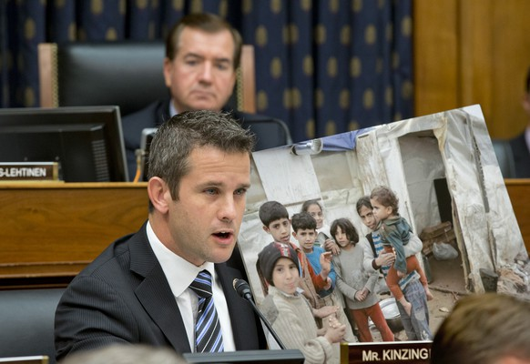 Rep. Adam Kinzinger, R-Ill., displays a photo of Syrian children while questioning Secretary of State John Kerry at a House Foreign Affairs Committee hearing on President Barack Obama's request for congressional authorization for military intervention in Syria, a response to last month's alleged sarin gas attack in the Syrian civil war, on Capitol Hill in Washington, Wednesday, Sept. 4, 2013. Chairman Ed Royce, R-Calif., listens at top.  (AP Photo/J. Scott Applewhite)