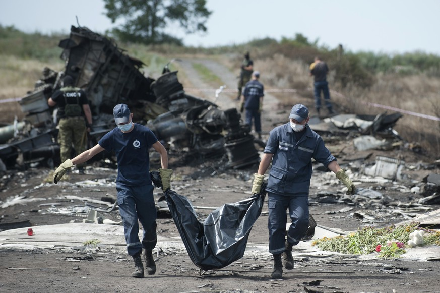 FOR STORY UKRAINE MH17 WHERE THINGS STAND - FILE - In this Sunday, July 20, 2014 file photo Ukrainian Emergency workers carry a victim's body in a body bag as pro-Russian fighters stand guard at the crash site of Malaysia Airlines Flight 17 near the village of Hrabove, eastern Ukraine. A year since a Malaysia Airlines Boeing 777 was blown out of the sky over war-ravaged eastern Ukraine, killing 298 people, there has been little definitive progress in determining what brought down Flight MH17. (AP Photo/Evgeniy Maloletka, file)