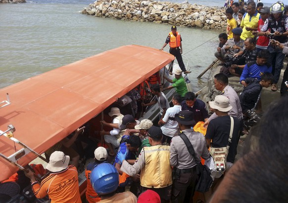 Rescue workers, police and residents prepare to unload the body of a ferry victim in Kolaka, South East Sulawesi, Indonesia December 20, 2015 in this photo taken by Antara Foto. Hopes faded on Sunday for 78 people missing from the ferry that sank off Indonesia's eastern island of Sulawesi, officials said, after 37 passengers were pulled alive from rough seas by rescuers in helicopters, fishing vessels and rubber dinghies. Three people have been found dead in the Gulf of Bone off South Sulawesi since the vessel with 118 on board ran into trouble on Saturday.   REUTERS/Sulaeman/Antara Foto ATTENTION EDITORS - THIS IMAGE HAS BEEN SUPPLIED BY A THIRD PARTY. IT IS DISTRIBUTED, EXACTLY AS RECEIVED BY REUTERS, AS A SERVICE TO CLIENTS. FOR EDITORIAL USE ONLY. NOT FOR SALE FOR MARKETING OR ADVERTISING CAMPAIGNS MANDATORY CREDIT. INDONESIA OUT. NO COMMERCIAL OR EDITORIAL SALES IN INDONESIA.