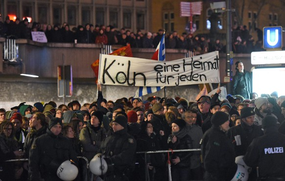 epa04560183 Participants march with a banner that reads 'Cologne home for all', during a rally in demonstration against the anti-Islam movement 'Koegida', in Cologne, Germany, 14 January 2015, a week after the terrorist attack on the satirical magazine 'Charlie Hebdo' in Paris.  EPA/HENNING KAISER