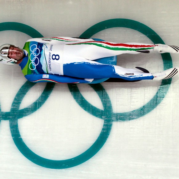 FILE - In this Sunday, Feb. 14, 2010 Armin Zoeggeler of Italy speeds past the Olympic rings during the third run of the men's singles luge competition at the Vancouver 2010 Olympics in Whistler, British Columbia. Luge standout Armin Zoeggeler, the first athlete to win a medal in the same individual event at six consecutive Olympics, has announced his retirement. The 40-year-old Zoeggeler revealed his plans at a news conference Tuesday, Oct. 14, 2014. Zoeggeler began his Olympic streak by winning bronze in singles at the 1994 Lillehammer Games. Then he took silver in Nagano four years later, gold in Salt Lake City and gold again at his home Turin Games, before concluding his career with bronzes in Vancouver and Sochi. Zoeggeler also won six golds and 16 medals overall at the world championships. (AP Photo/Elise Amendola, File)