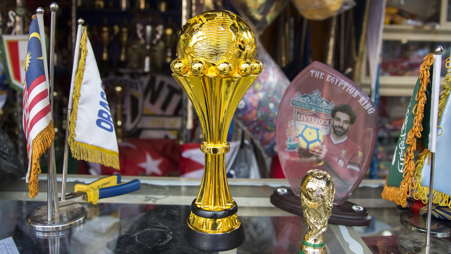 epa07647762 African cup of nation statue displayed with a photo of Mohamed Salah the Egyptian footballer for sale at a shop as preparation for the African cup in downtown Cairo, Egypt,  14 June 2019. Egypt will host the African Cup of Nations, which has been expanded to 24 teams, from 21 June to 19 July.  EPA/Mohamed Hossam