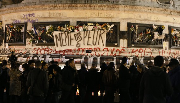 epa05027465 A sign reads 'Not even afraid', draped on the statue on Place de la Republique in Paris, France, 15 November 2015. At least 132 people were killed in a series of attacks in Paris on 13 November, according to French officials. Eight assailants were killed, seven when they detonated their explosive belts, and one when he was shot by officers, police said. French President Francois Hollande says that the attacks in Paris were an 'act of war' carried out by the Islamic State extremist group.  EPA/IAN LANGSDON