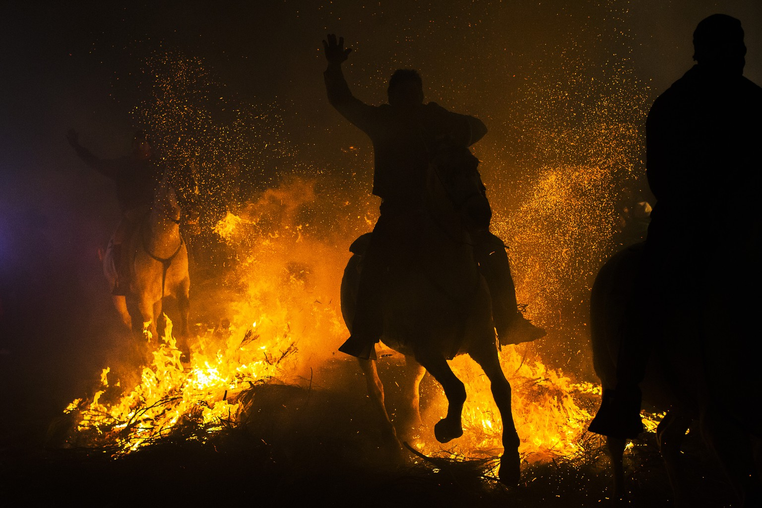 Men ride horses through a bonfire as part of a ritual in honor of Saint Anthony the Abbot, the patron saint of domestic animals, in San Bartolome de Pinares, about 100 kilometers (62 miles) west of Madrid, Spain on Friday, Jan. 16, 2015. On the eve of Saint Anthony's Day, hundreds ride their horses through the narrow cobblestone streets of the small village of San Bartolome during the