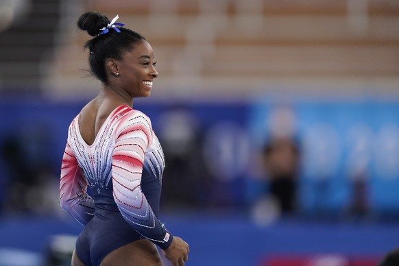 Simone Biles, of the United States, smiles during the warm up prior to the artistic gymnastics balance beam final at the 2020 Summer Olympics, Tuesday, Aug. 3, 2021, in Tokyo, Japan. (AP Photo/Ashley Landis)