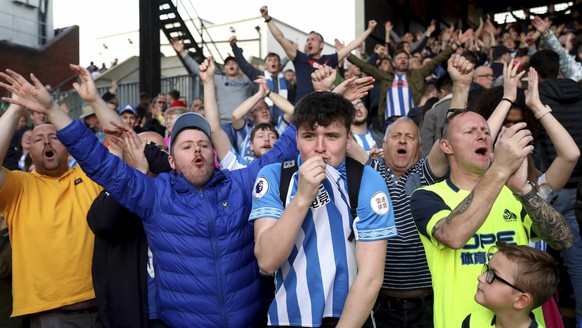 Huddersfield Town fans applaud their team after their relegation was confirmed after the English Premier League soccer match between Crystal Palace and Huddersfield Town at the Selhurst Park stadium, London. Saturday, March. 30, 2019 (Isabel Infantes/PA via AP)