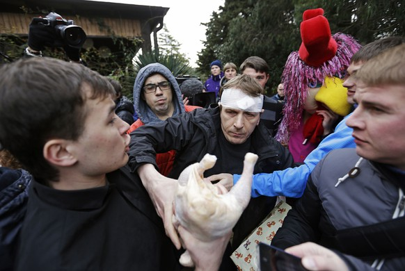 Pussy Riot member Alexei Knedlyakovsky, center, tries to wrestle a chicken away from protestors of the punk group - who have feuded with Vladmir Putin's government for years -  during a press conference, Thursday, Feb. 20, 2014, in Sochi, Russia. (AP Photo/David Goldman)