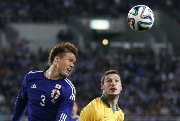 Gotoku Sakai (L) of Japan fights for the ball against Mathew Leckie of Australia during their international friendly soccer match in Osaka, western Japan November 18, 2014.  REUTERS/Thomas Peter (JAPAN - Tags: SPORT SOCCER)