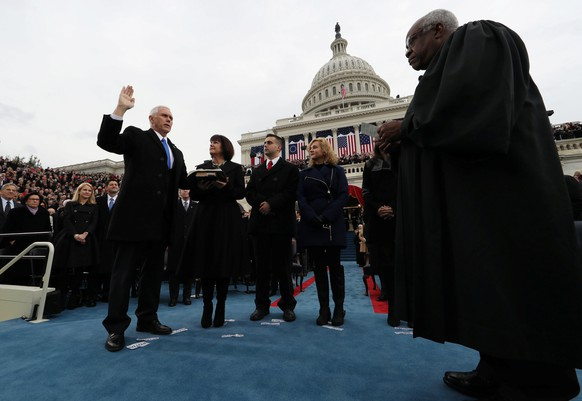 U.S. Vice President Mike Pence takes the oath of office as his wife Karen, son Michael and daughter Charlotte look on as U.S. Supreme Court Justice Clarence Thomas (R) administers the oath during inauguration ceremonies swearing in Trump as the 45th president of the United States on the West front of the U.S. Capitol in Washington, DC, U.S., January 20, 2017.  REUTERS/Jim Bourg