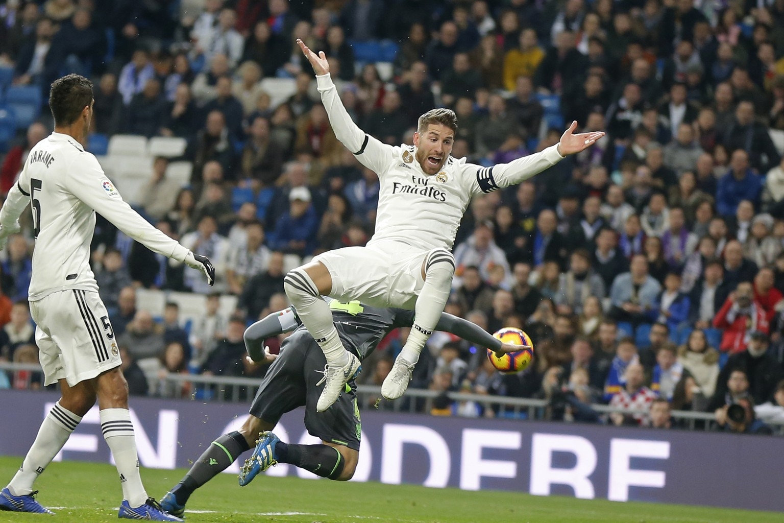 Real Madrid's Sergio Ramos jumps, with Real Sociedad's Asier Illarramendi, obscured behind, during a Spanish La Liga soccer match between Real Madrid and Real Sociedad at the Santiago Bernabeu stadium in Madrid, Spain, Sunday, Jan. 6, 2019. (AP Photo/Paul White)