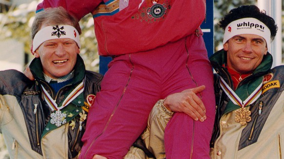 DOWNHILL MEDALIST: Downhill Gold medalist Hansjoerg Tauscher, of West Germany, rides the shoulders Switzerlands second place finisher Peter Mueller (left) and Karl Alpinger at the World Alpine Championships medal presentation ceremony in Vail (Colorado), Beaver Creek on Februar 06, 1989. (AP-Photo/stf/Rudi Blaha)