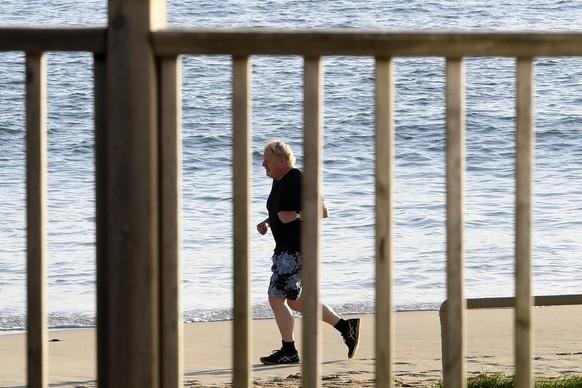 Britain's Prime Minister Boris Johnson runs along the beach in Carbis Bay, Cornwall, England, Saturday June 12, 2021, during the G7 summit in Cornwall. (Stefan Rousseau/Pool via AP)