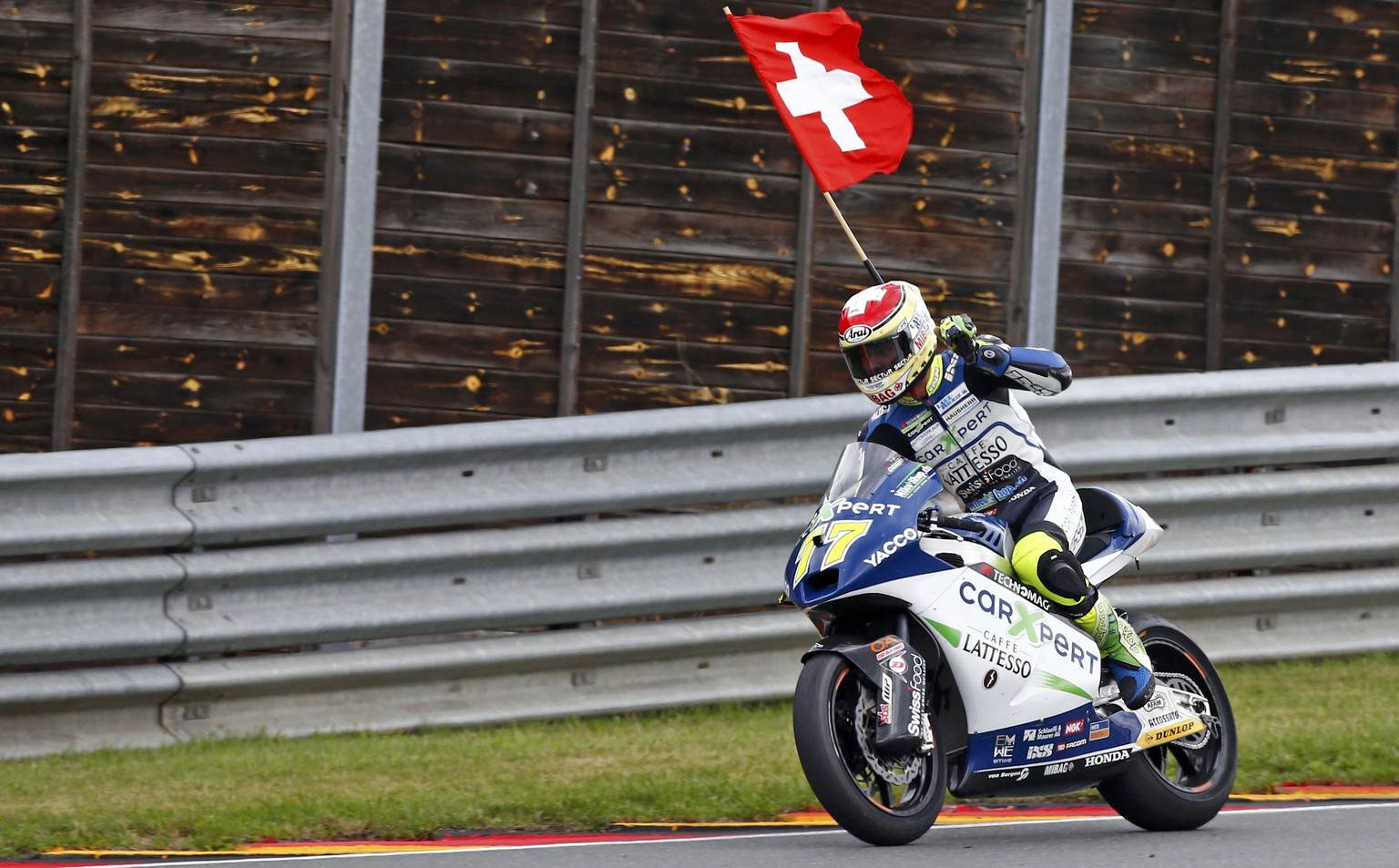Winner Suter Moto2 rider Dominique Aegerter of Switzerland celebrates during the German Grand Prix at the Sachsenring circuit in the eastern German town of Hohenstein-Ernstthal July 13, 2014. REUTERS/Thomas Peter (GERMANY  - Tags: SPORT MOTORSPORT)