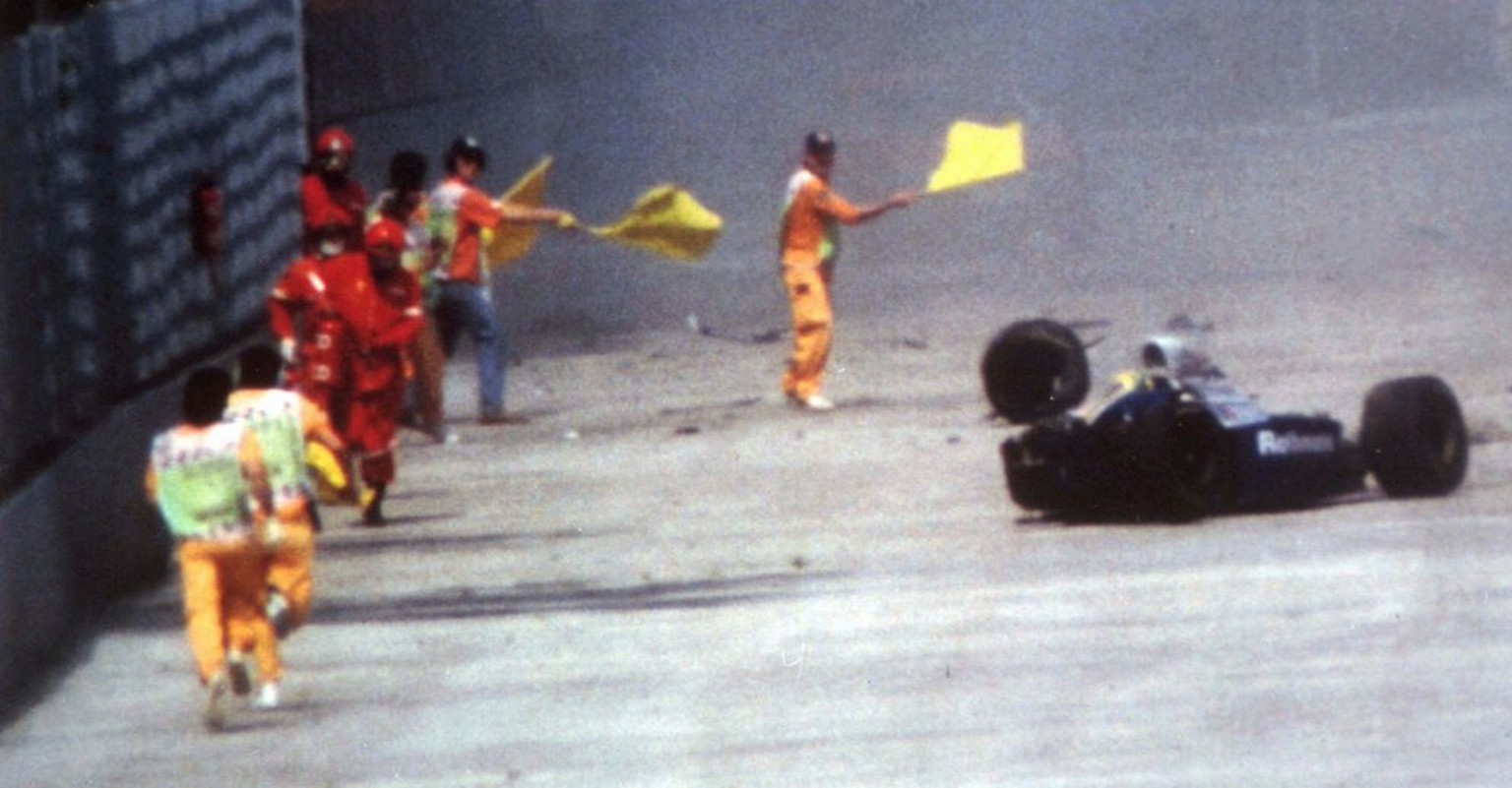 Race officials run toward Brazil's Aytron Senna after he crashed with his Williams-Renault during the San Marino F-1 Grand Prix in Imola Sunday May 1, 1994.  Senna died at a Bologna hospital later. Nearly three years after the fatal crash, six top Formula One figures, including Frank Williams, head of the successful Williams-Renault team, face manslaughter carges in a trial starting in Imola Thursday, February 20, 1997. (KEYSTONE/AP/PESCI)