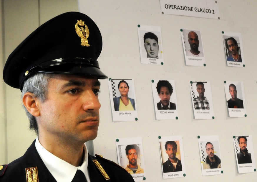 An Italian Police officer stands next to mug shots of alleged migrant traffickers shown during a press conference, in Palermo, Sicily, Italy, Monday, April 20, 2015. Police in southern Italy has broken up a major human smuggling ring responsible for the waves of migrants reaching Italian shores, and have detailed how the traffickers make money through illicit payments from desperate migrants willing to make the deadly crossings. Palermo Prosecutor Maurizio Scalia told reporters that the arrest warrants have been issued against 24 people, 14 of them in Italy but at least one of them at large in Libya. (AP Photo/Alessandro Fucarini)