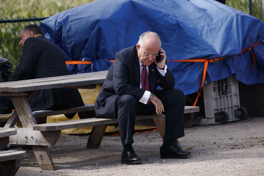 Former New York Mayor Rudy Giuliani speaks on the phone outside a meeting between Republican presidential candidate Donald Trump and local farmers at Bedners Farm Fresh Market, Monday, Oct. 24, 2016, in Boynton Beach, Fla. (AP Photo/ Evan Vucci)