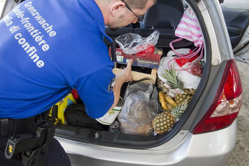 A Swiss border guard controls in the trunk of a Swiss car the goods purchased in a French supermarket close to the border at the Swiss-French border of Bardonnex near Geneva, Switzerland, Tuesday, August 16, 2011. (KEYSTONE/Salvatore Di Nolfi)