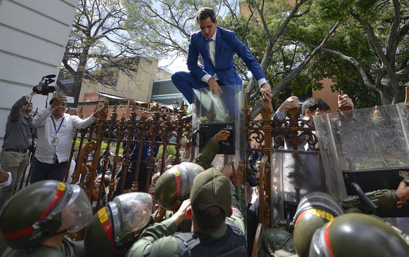 National Assembly President Juan Guaido, Venezuela's opposition leader, climbs the fence in a failed attempt to enter the compound of the Assembly, as he and other opposition lawmakers are blocked from entering a session to elect new Assembly leadership in Caracas, Venezuela, Sunday, Jan. 5, 2020. With Guaido stuck outside, a rival slate headed by lawmaker Luis Parra swore themselves in as leaders of the single-chamber legislature. (AP Photo/Matias Delacroix)